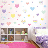 Heart wall stickers stuck on cream wall in girl theme bedroom above cupboard.