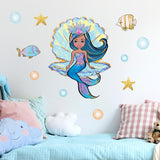 Mermaid wall stickers stuck on a cream bedroom wall above a childs blue bed.