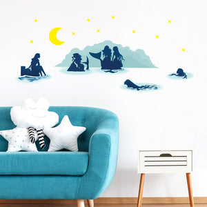 Mermaid wall stickers stuck on white wall above a blue sofa. Sofa has star an cloud shaped cushions on it.