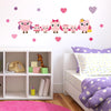 Pink family owls wall stickers stuck above girls bed on pink wall. Girls bed is pink an purple colour.