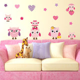 Pink family owls wall stickers stuck on living room wall, above sofa. Wall is cream sofa is pink purple pillows.