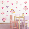Pink family owls wall stickers stuck on playroom wall. Wall is pink, kids chair is pink purple colour.
