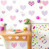 Heart wall stickers stuck on white wall above desk. Girl theme bedroom.