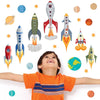 Toddler looking upwards at robots in space wall stickers set. wall decals are stuck on wall above toddler