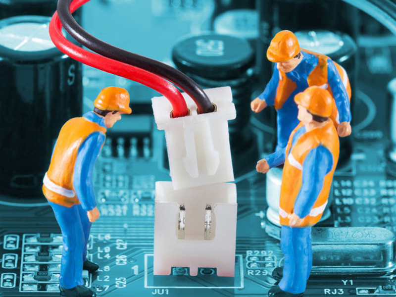 Technician figurines examining wires on motherboard