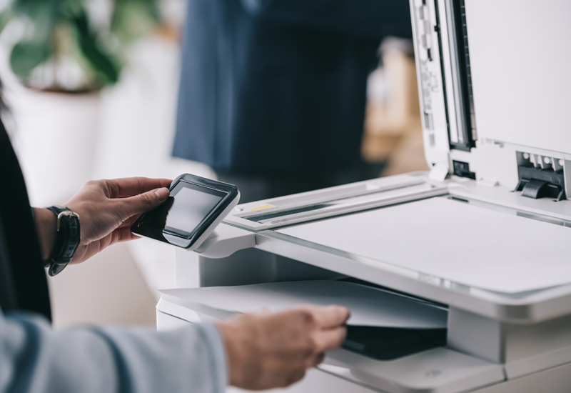 Cropped view of man using multifunction office copier