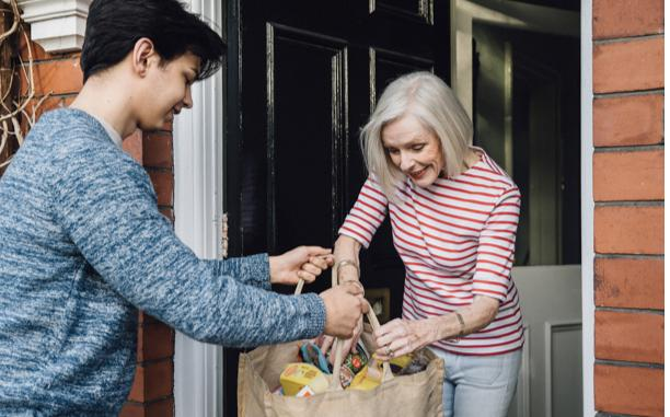 Young man delivering groceries to senior woman
