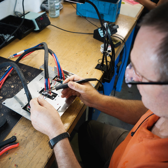 A person doing soldering work on a circuit board