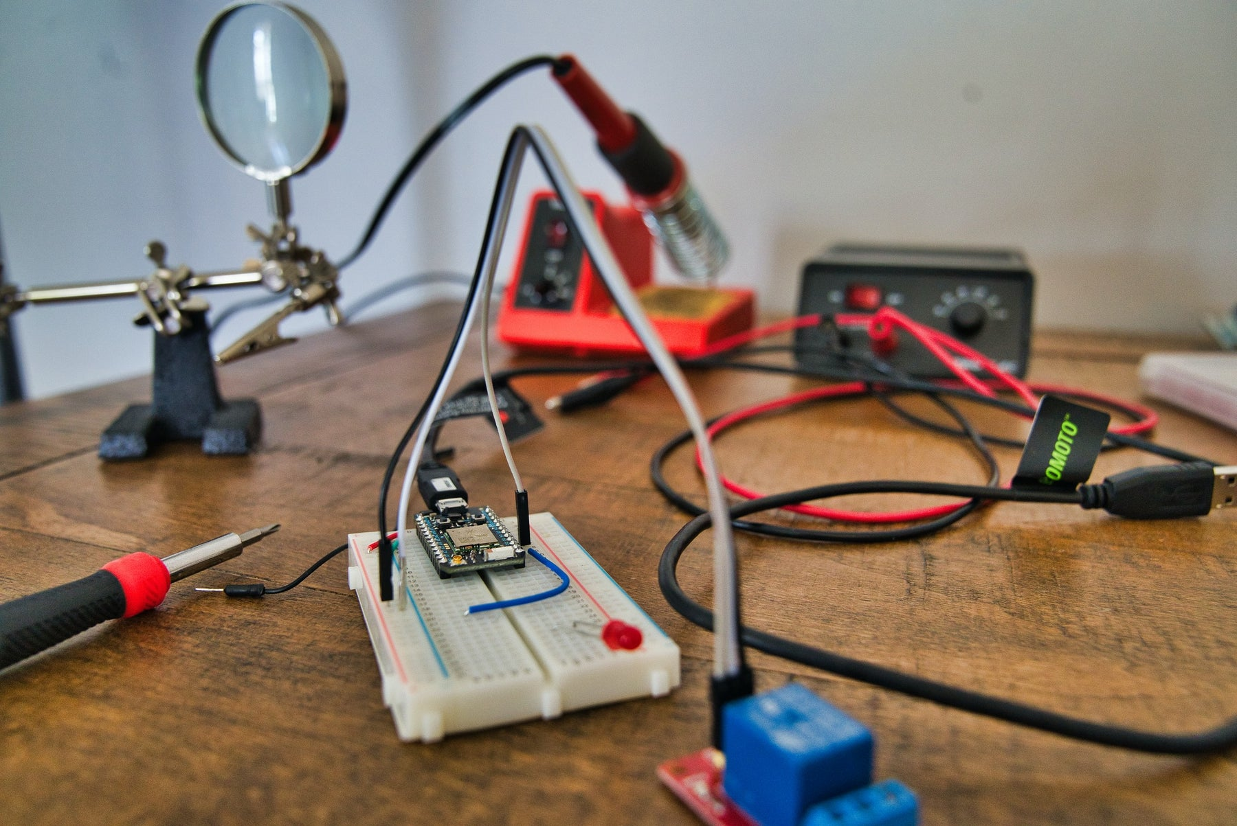 Soldering iron with red handle and other essential electronic equipment arranged on a table