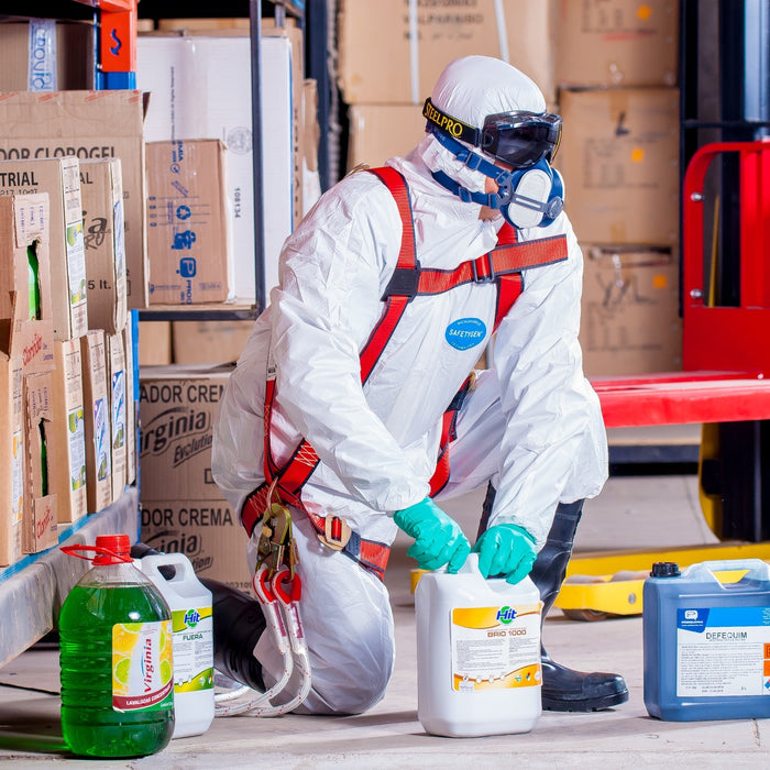 A person wrapped in a white smock and ESD-safe protective equipment handling chemicals
