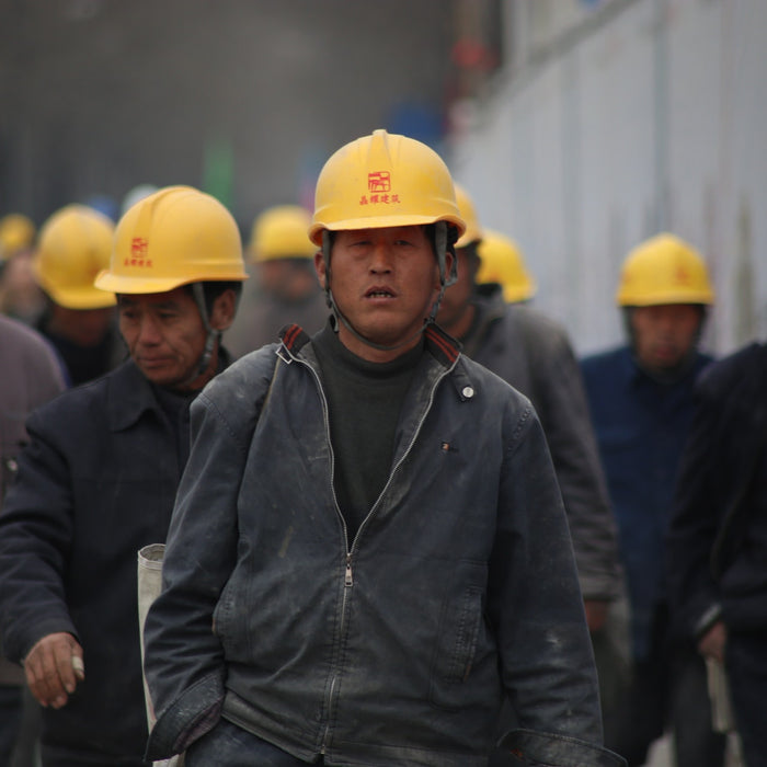 A group of industrial workers in grey jackets