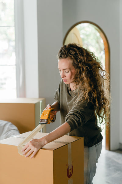 A young lady using an adhesive tape to to pack a cardboard