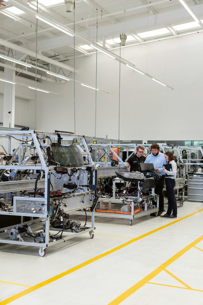 Three people verifying the product quality inside a large manufacturing unit