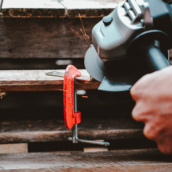 A man fixing a red color clamp on a wooden material
