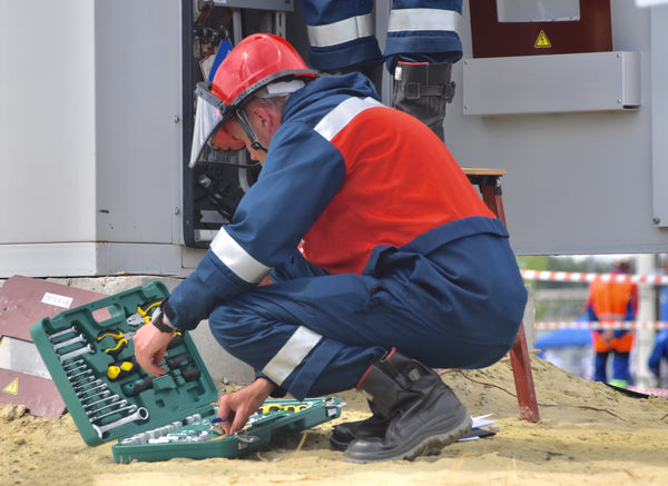 A man dressed in a safety garment searching for tools from a toolbox