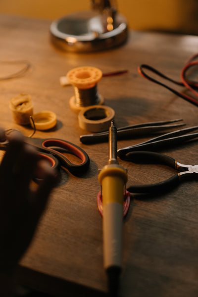 A wooden table with the soldering iron, tweezer, scissors, and ceramic cream