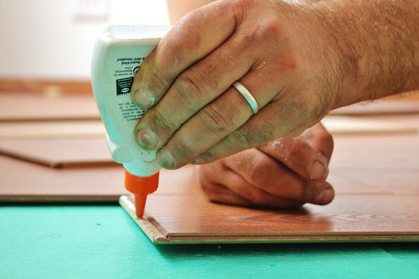 A person applying glue on a wooden surface