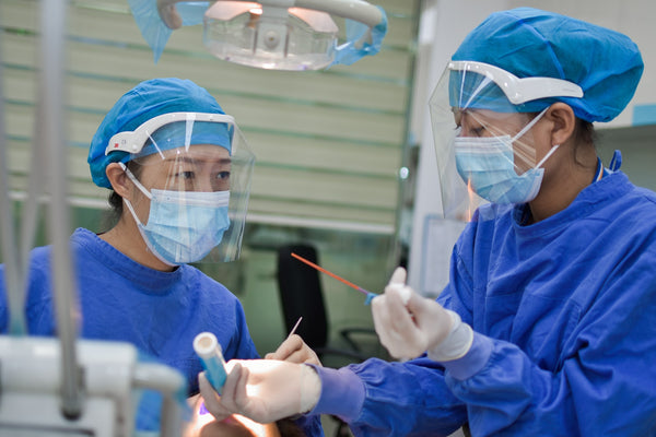 Two women in blue PPE holding surgical equipment