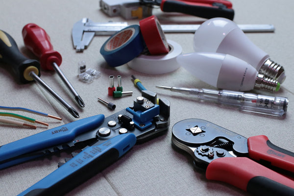 A collection of essential hand tools with screwdrivers, spanner, plier, and insulation tapes