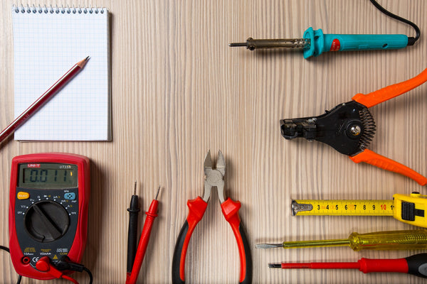 A collection of essential handheld tools arranged neatly on a table