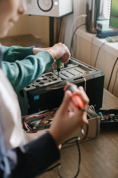 A boy in a black sleeve holding a red handled soldering iron