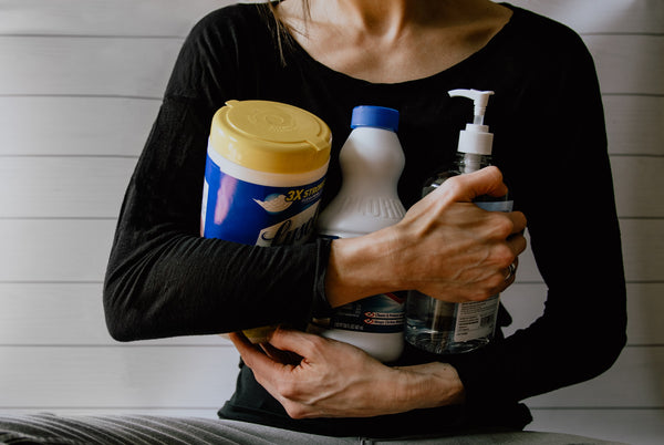 A woman in a black dress holding sanitizer, disinfectant, and cleaners