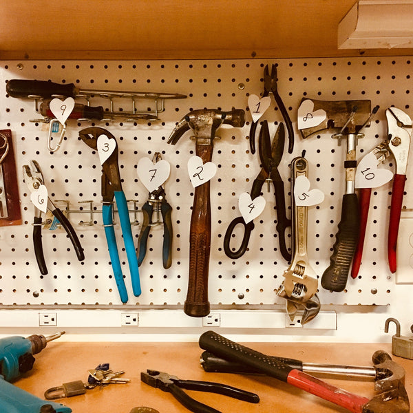 Hammer, pliers, tweezers, and other essential equipment arranged neatly on a workbench