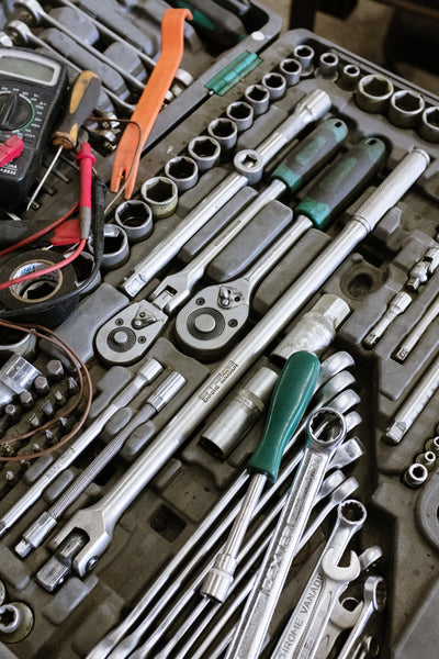 A toolkit with essential equipment like pliers, screwdrivers,  tweezers, and wenches