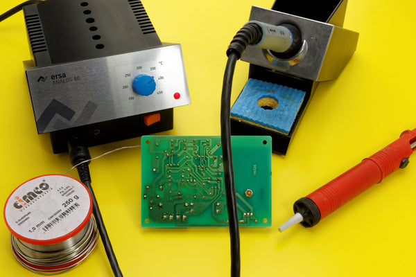 A desoldering iron, neatly coiled steel wire and circuit board arranged on a yellow background