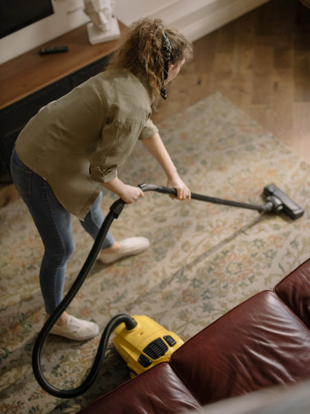 A woman in green top cleaning the room using a vacuum cleaner