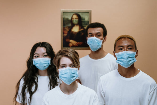 Two women and two men in a white T-shirt with nitrile blue face masks