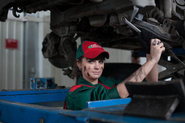 A woman in green and red workwear at an automobile industry