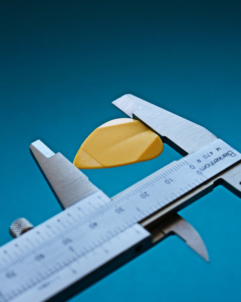 A steel calliper measuring the diameter of a yellow object
