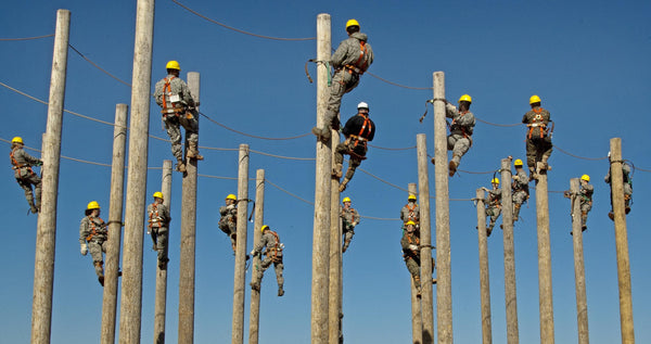 Electric workers in workwear climbing on transformers