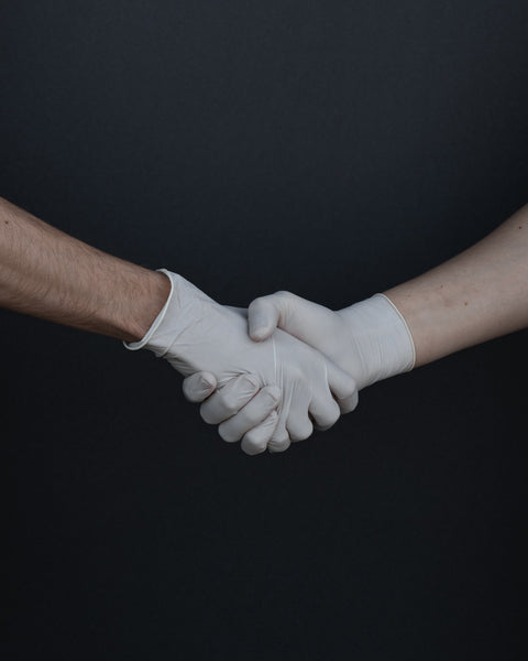 Two person wearing white gloves shaking hands