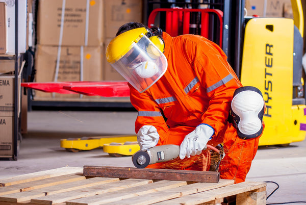 A man in orange ESD safe dress, head cap, and white gloves working inside a manufacturing unit