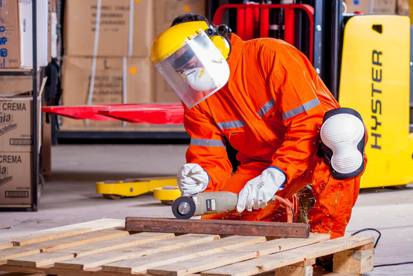 An industrial worker wrapped inside an orange color protective wear doing manufacturing works