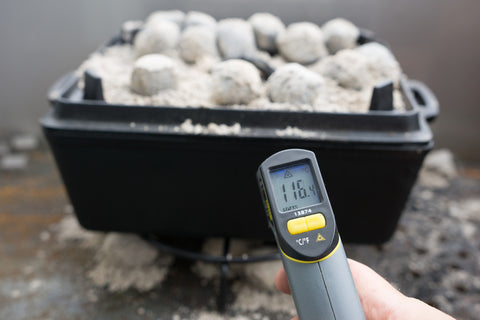 A person measuring the temperature using an industrial thermometer