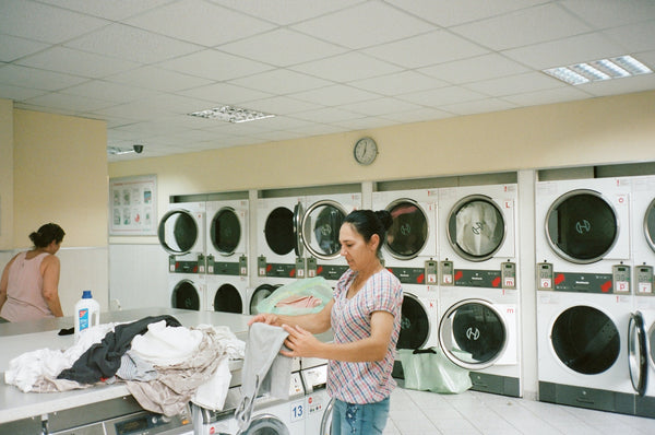 Two women working inside laundry to ensure safe wash of protective garments