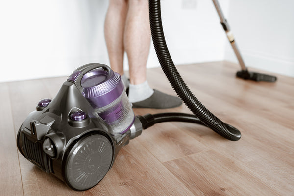 A person using a vacuum cleaner to clean the floor