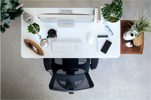 A workspace with a black upholstered chair, a laptop, and essential office accessories