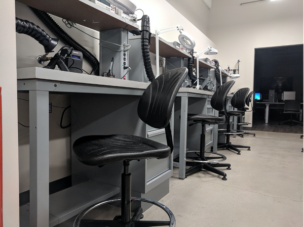 Bevco chairs in work area featuring multiple workbenches with soldering and rework.
