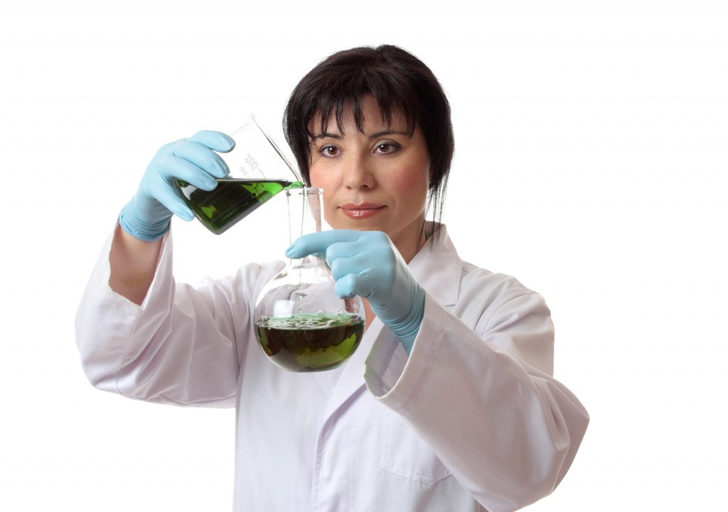 A scientist pouring chemical into a round flask.