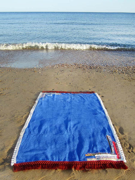 Beach towel in royal blue color with woven ribbons and tassels