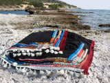 Beach towel in black color with woven ribbons and tassels