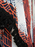 Caftan dress in white color with geometric and abstract pattern and navy blue and neon coral hues and black fringed ribbon