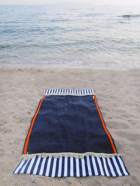 Beach towel in navy blue color with two extra panels of striped cotton fabric on its sides and cotton fringes