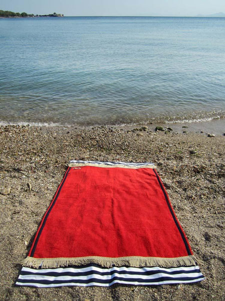 Beach towel in red color with two extra panels of striped cotton fabric on its sides and cotton fringes