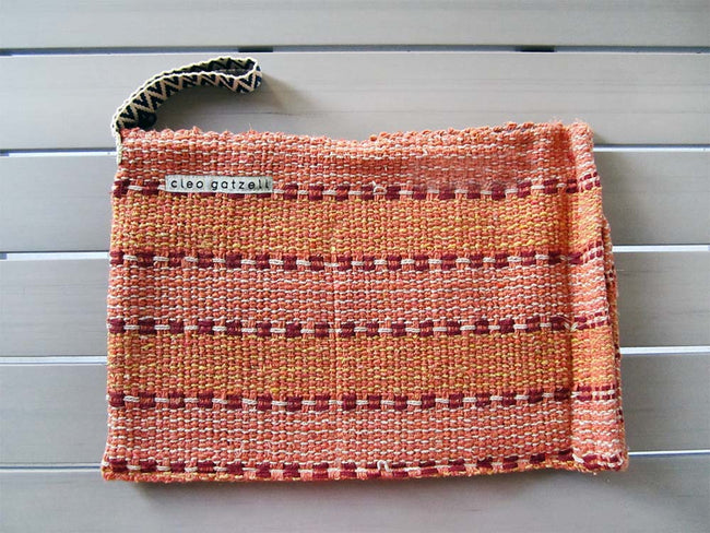 Rug clutch bag in orange color and stripes