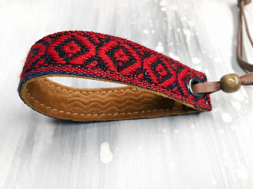 Leather bracelet with a red woven ribbon and Aztec pattern